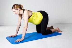 Pregnant woman kneeling on mat